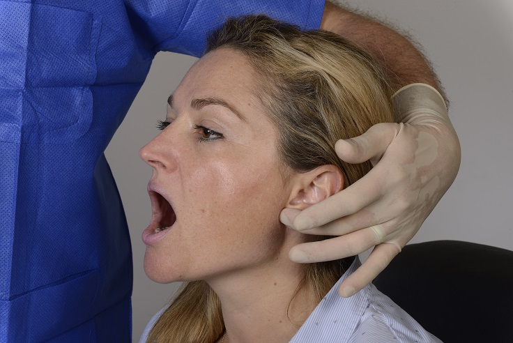 The dentist locates the ear lobe and the posterior edge of the mandibular ramus.